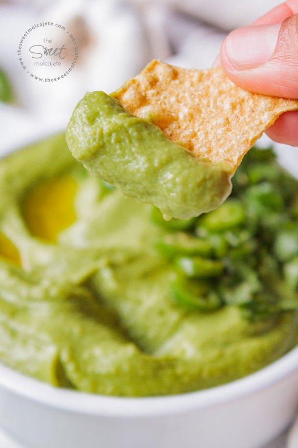 Mano agarrando un totopo con Hummus Verde de Cilantro con Chile