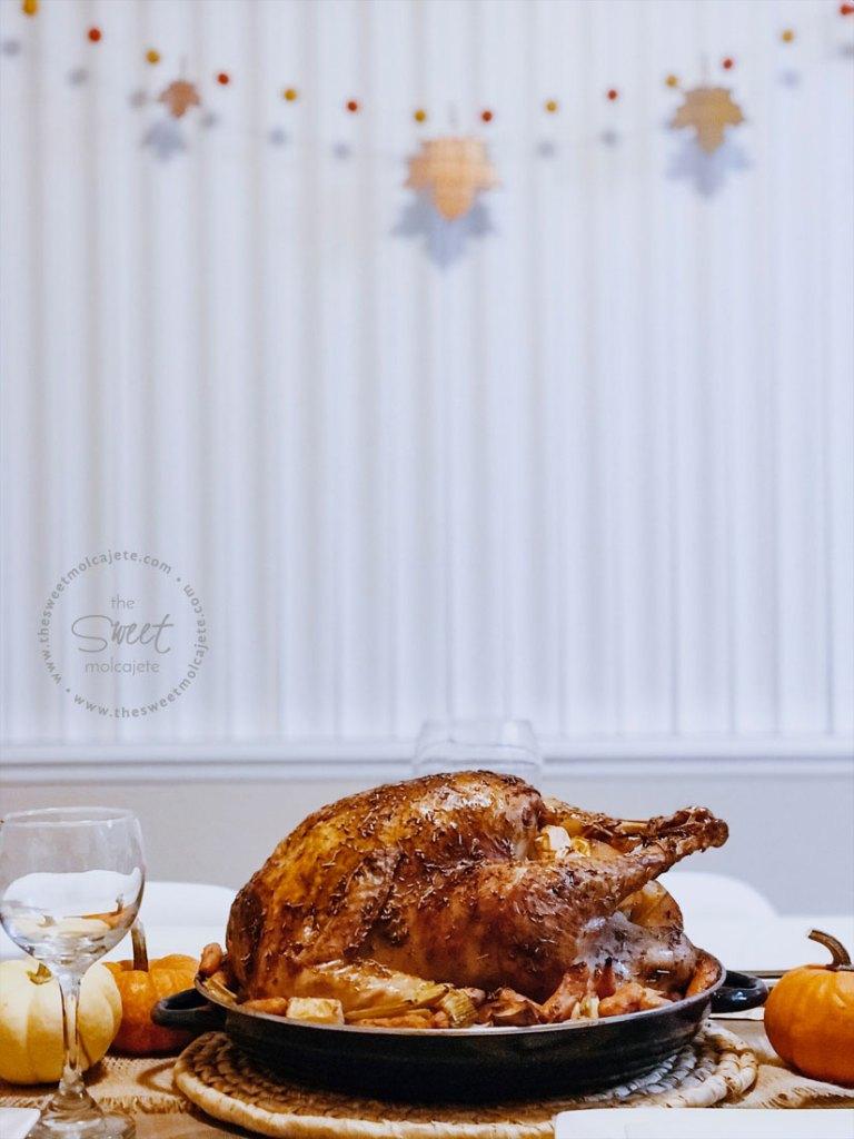 Pavo al horno con Citricos y Romero sobre una cama de verduras en una mesa lista para la cena de Navidad