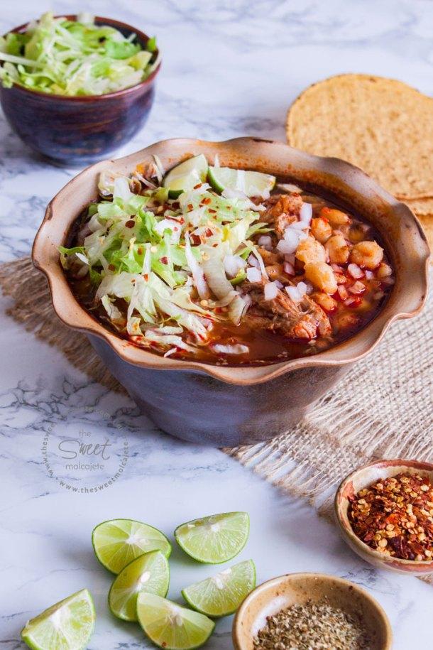Plato de Pozole Rojo con carne de cerdo con lechuga, cebolla, chile y limón