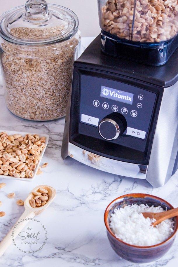 Licuadora vitamix con cacahuate adentro del vaso y en la mesa ingredientes para hacer bolitas de cacahuate con chocolate