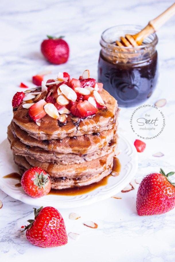 Plato con cinco Hotcakes Integrales con Avena y Chispas de Chocolate con miel, fresas y almendras