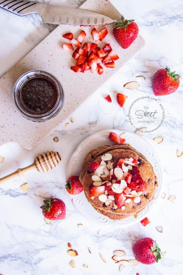 Vista aérea de un plato con Hotcakes Integrales con Avena con fresas y almendras y un tarro de miel a lado