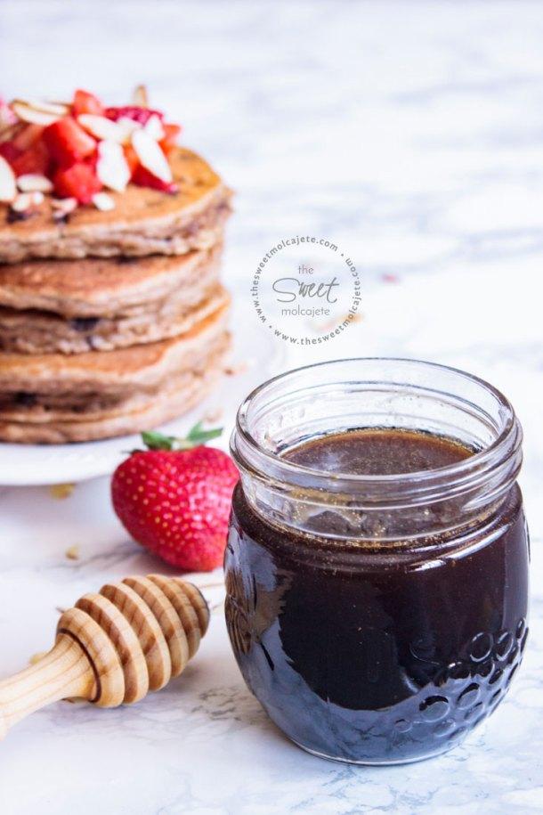 Frasco con jarabe casero sabor maple con una palita mielera a lado y un altero de pancakes detrás