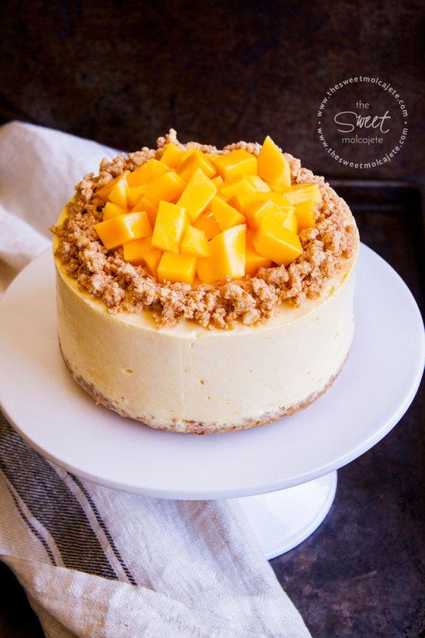 Cheesecake de mango sin horno sobre un cake stand blanco en un fondo oscuro rústico