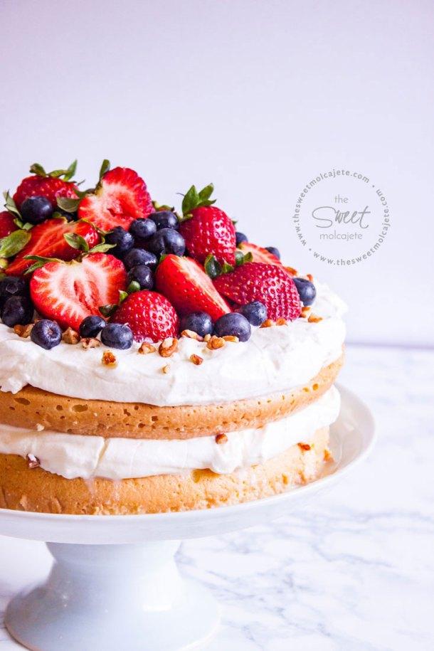 Pastel de tres leches en un pedestal de cerámica, el pastel está cubierto con crema batida, fresas, moras y nuez