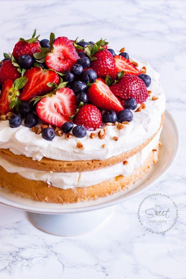 Acercamiento a un pastel de tres leches en dos capa, es un naked cake cubierto y relleno con crema batida y decorado con fresas, nueces y moras