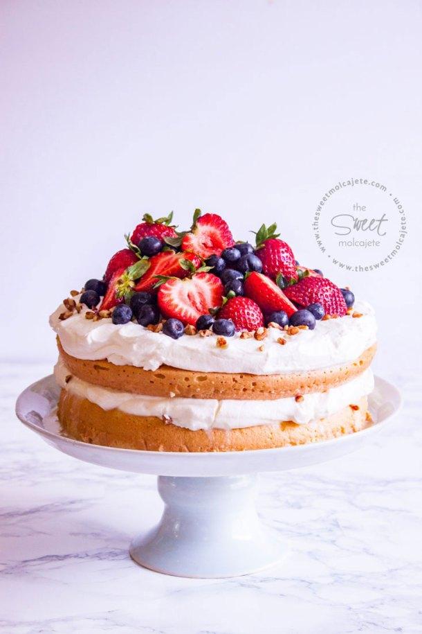 Pastel de tres leches en dos capas con relleno y cobertura de crema batida y fresas y moras arriba