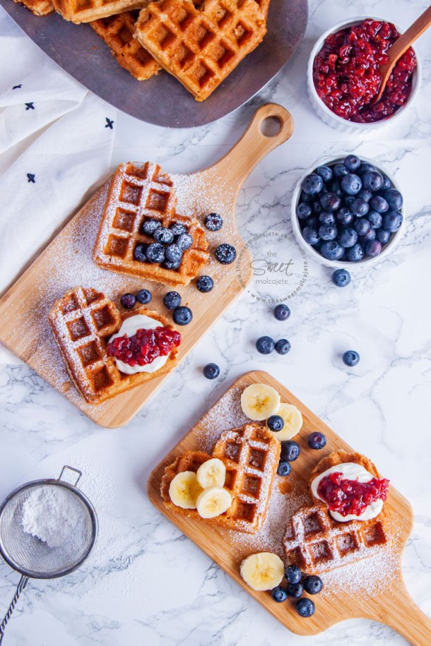 Waffles de corazon en tablitas de madera con fruta, crema batida y azucar