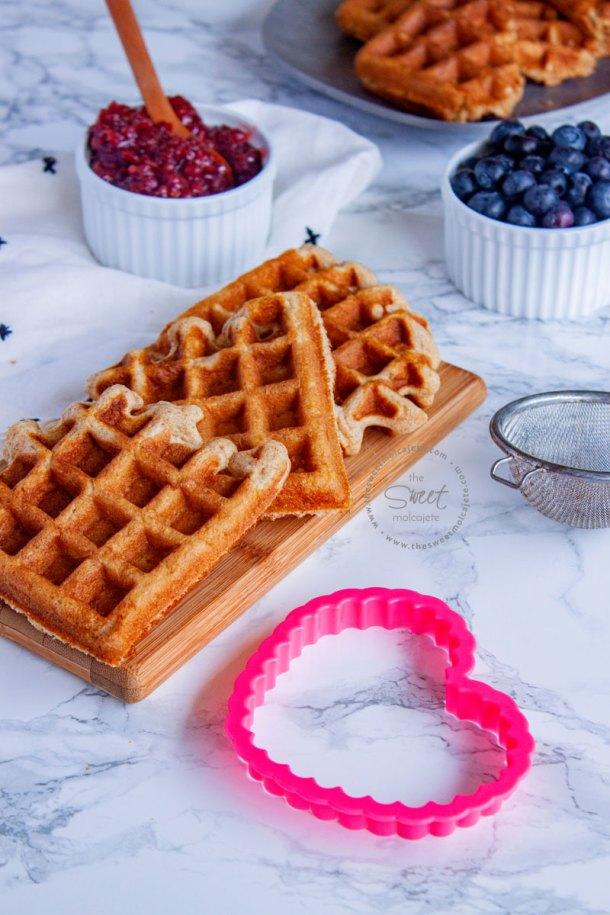 waffles integrales en una tablita y un cortador de galleta en forma de corazon a un lado