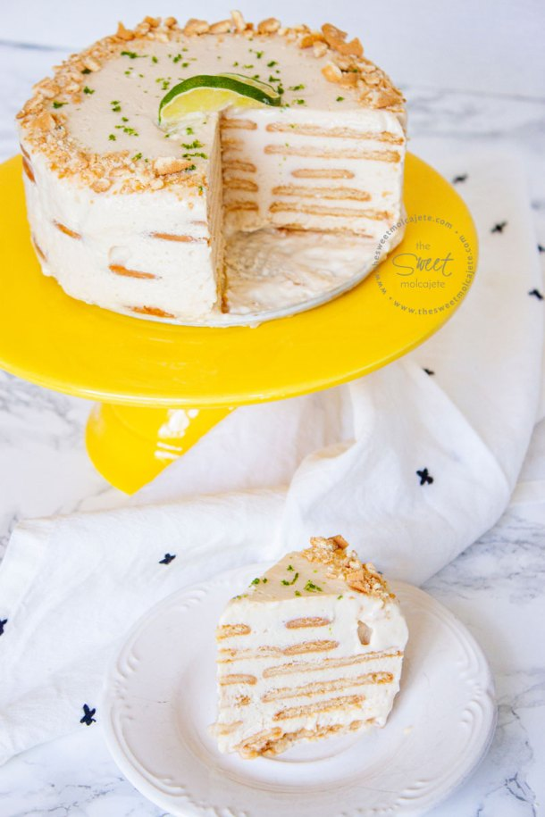 Carlota de Limón en forma de pastel ya partido en un cakestand amarillo y una rebanada al frente servida en un platito
