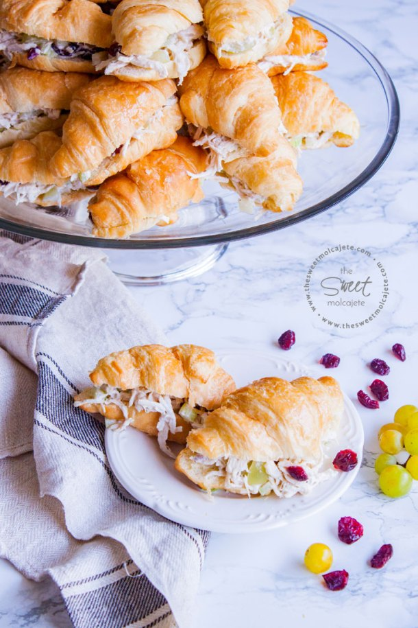 Plato grande lleno de sandwiches de cuernitos rellenos de ensalada de pollo con uvas