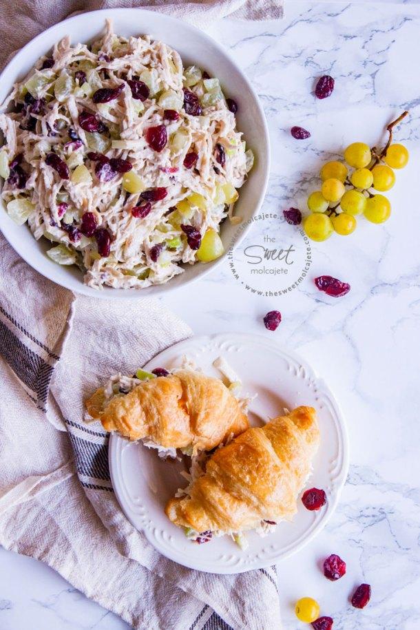 Vista de arriba a un plato con ensalada de pollo y dos sandwiches de cuernitos con esta ensalada. Hay un racimo de uvas verdes en la mesa