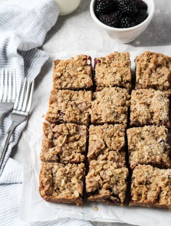 Blackberry bars with oat crumble topping cut into squares.