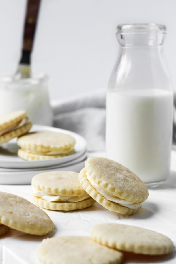 Lemon butter cookie sandwiches with lemon buttercream and a glass of milk.