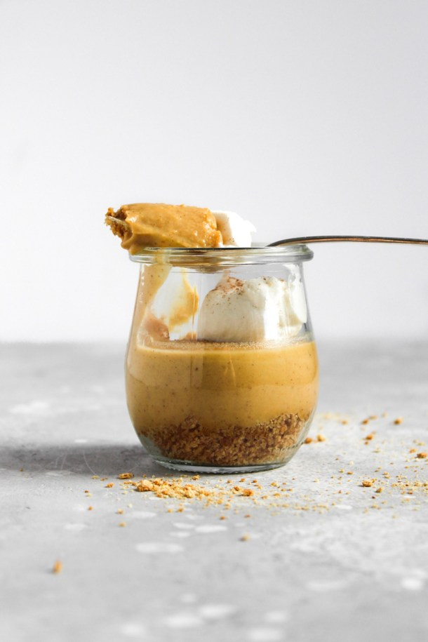 Side shot of pumpkin custard in a glass jar with a spoon of the custard laying on top of the jar.