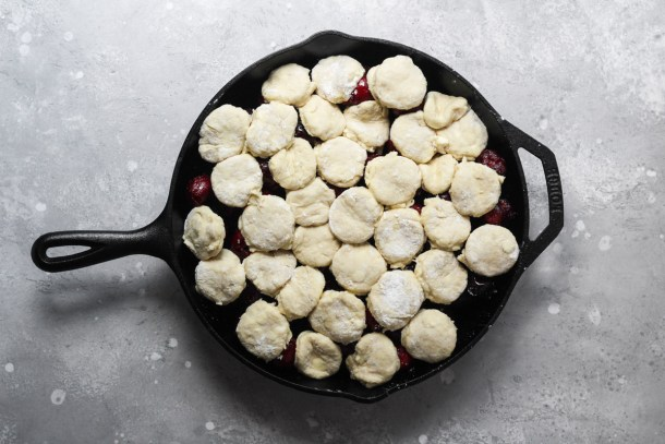 Cast iron skillet with unbaked cherry cobbler and homemade biscuits.