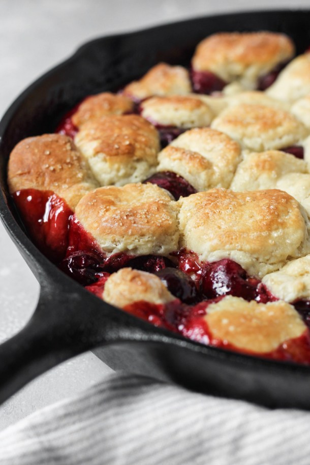 Cast iron skillet with cherry cobbler and homemade biscuits.