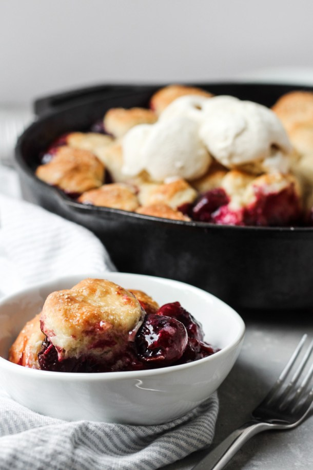Bowl of cherry cobbler with cream biscuits and vanilla ice cream