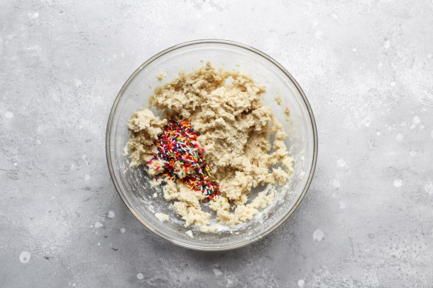 Edible cookie dough in a mixing bowl with sprinkles.