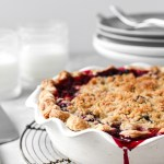 Mixed berry pie with crumb topping in pie dish on cooling rack.
