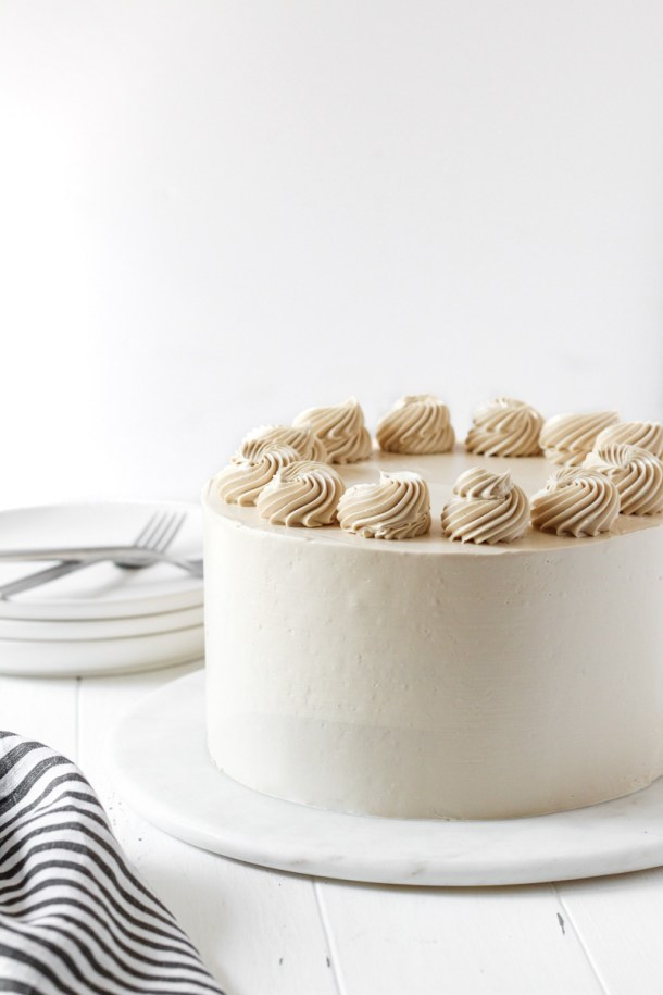 8-inch round apple cider cake with brown sugar Swiss meringue buttercream with rosettes on top.