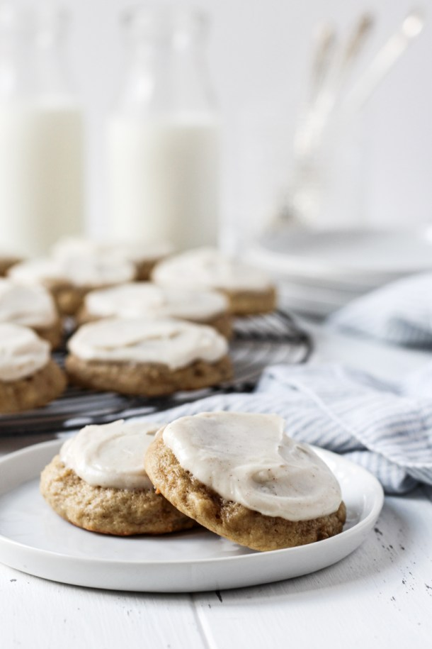 Two banana bread cookies topped with cream cheese frosting on a plate with more cookies on a French round wire rack, milk, and plates in the background.