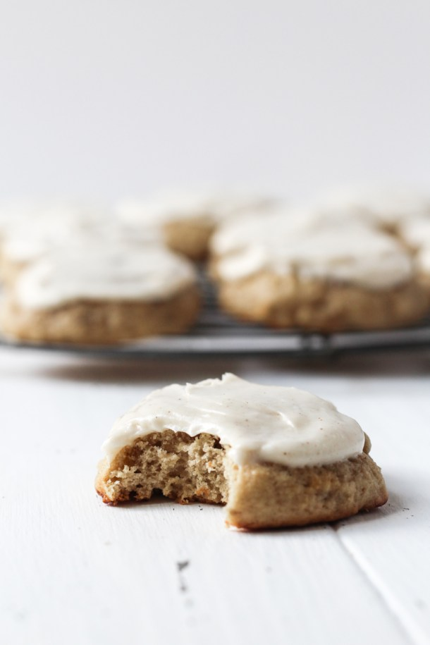 Banana bread cookie with cream cheese frosting on a white board with a bite taken out of it and a French wire rack of more cookies in the background.