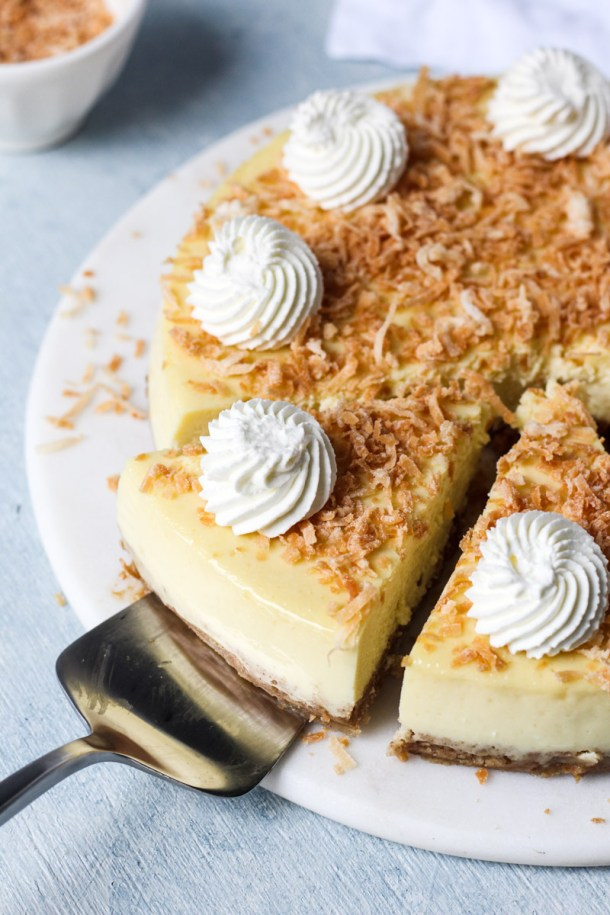Coconut cheesecake topped with toasted coconut and dollops of whipped cream. Pie server pulling one of the slice out of the cheesecake.