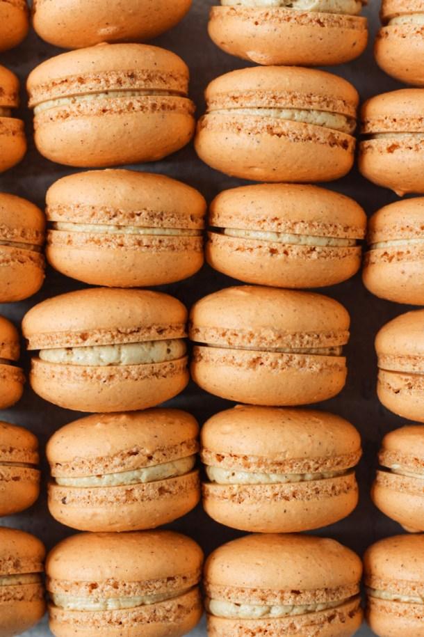 Overhead shot of columns of pumpkin macarons filled with pumpkin Swiss meringue buttercream.