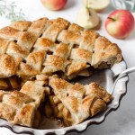 Chai apple pie with a lattice crust and half the pie sliced.