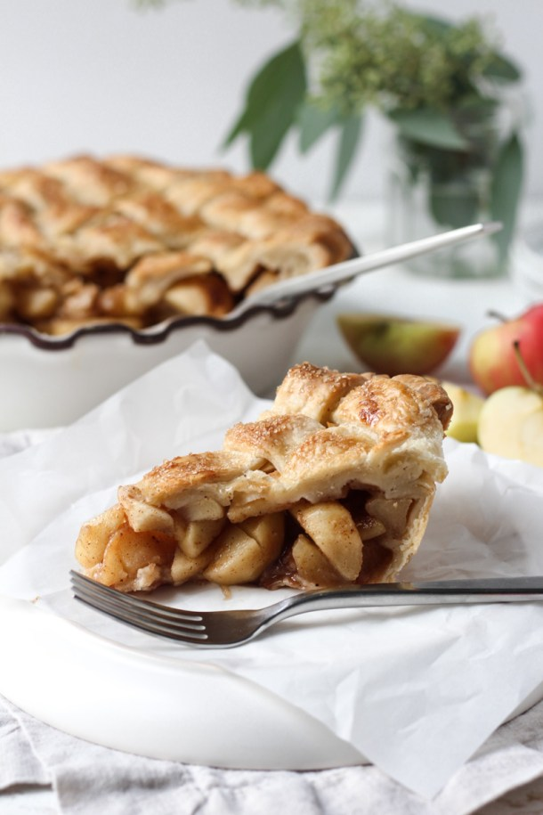 Slice of chai apple pie with lattice top with whole pie in the background.