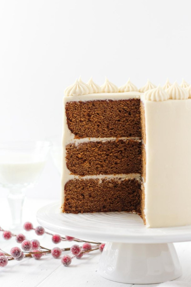 Gingerbread layer cake with brown sugar cream cheese frosting on a white cake stand with a slice removed to reveal the three layer.