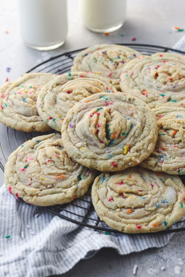 Stack of funfetti stuffed cookies with buttercream on a French wire rack.