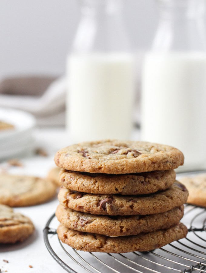 Stack of brown butter cookies with toffee bits on a French wire cooling rack with milk in the backgroud.