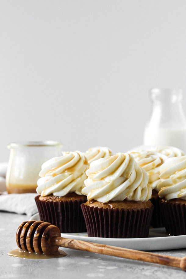 Plate of sweet potato cupcakes with salted maple caramel cream cheese frosting and a caramel drizzle.
