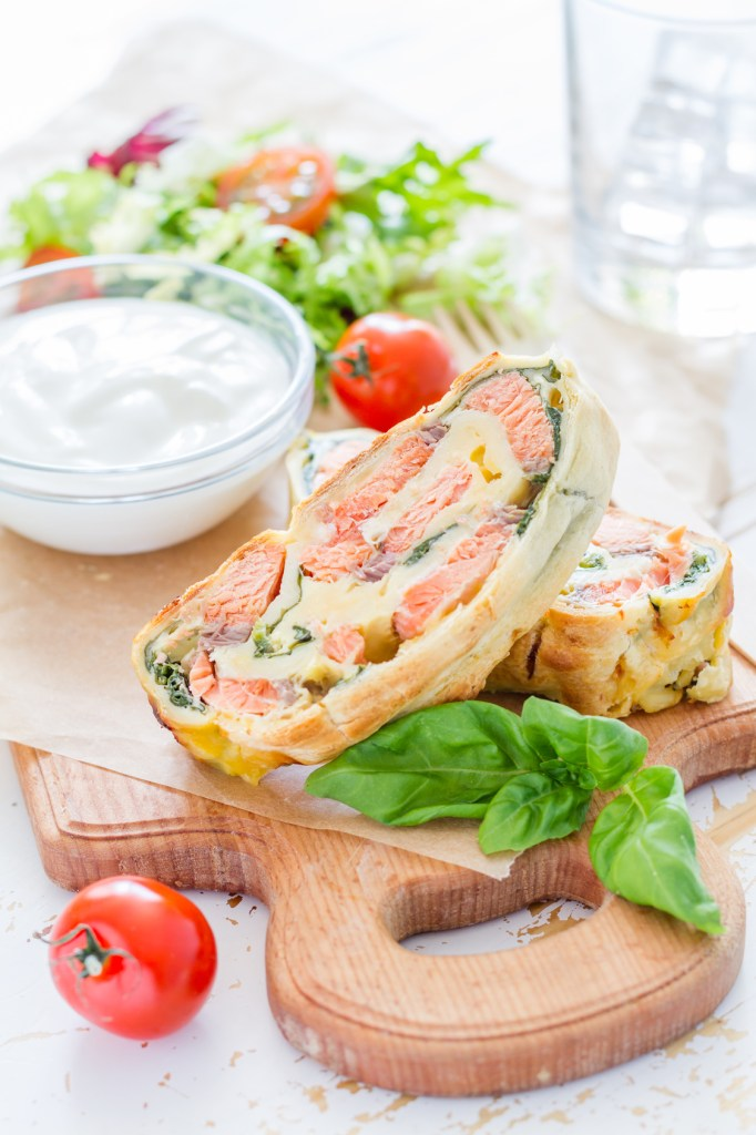 Salmon and spinach strudel on white wood background