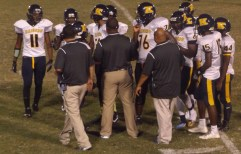 The offense coaches talk to the team during a timeout. File photo.