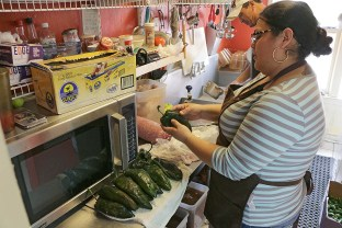 Mama's Kitchen cook Carmen Lopez adds cheese into poblano chiles for chile relleno. BRIANNA RODRIGUE / THE TACOIST