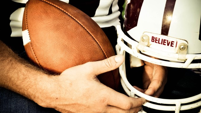 hero image: hands holding football and helmet that says believe over facemask