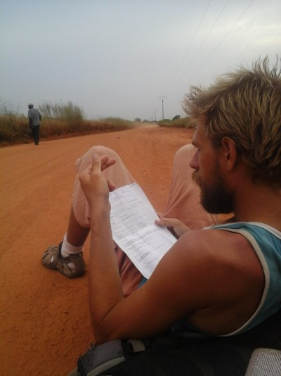 Blonde man sitting on the sand road reading a paper in Toubacuta