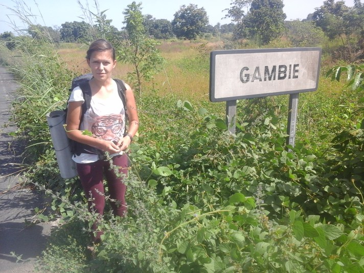 "female traveller standing on the road next to a sign that says ""Gambie"" while Traveling The Gambia"