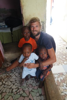 blone man with beard holding three African children in Senegal