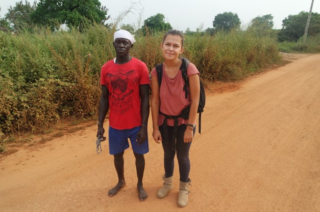 A woman standing next to an African men on a sandy road