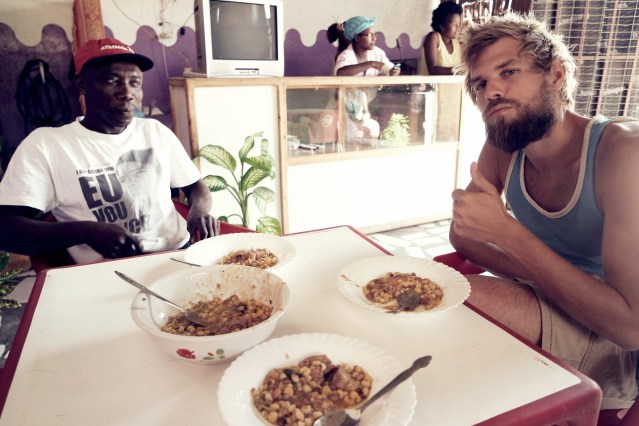 A German man eating Cachupa with an African man in a restaurant