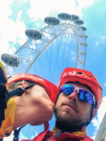 A woman wearing a helmet kissing a men wearing a helmet in front of the London eye, in the United Kingdom