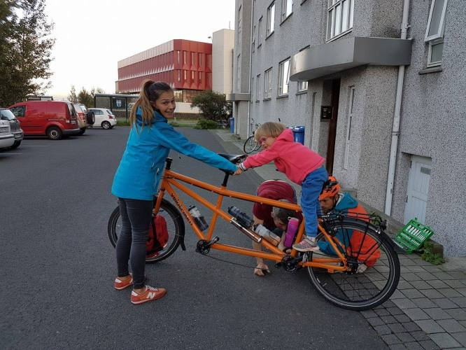 W child on a tandem bicycle and a woman holding the bicycle, in Iceland
