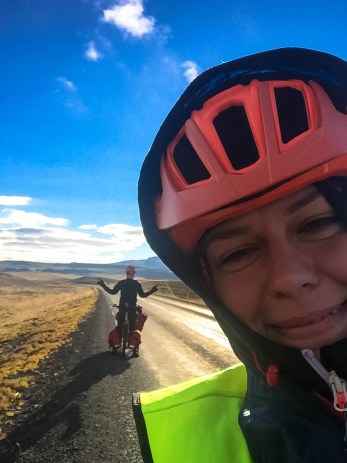 A posing man on a tandem bicycle and a woman wearing a helmet in the foreground, in Iceland