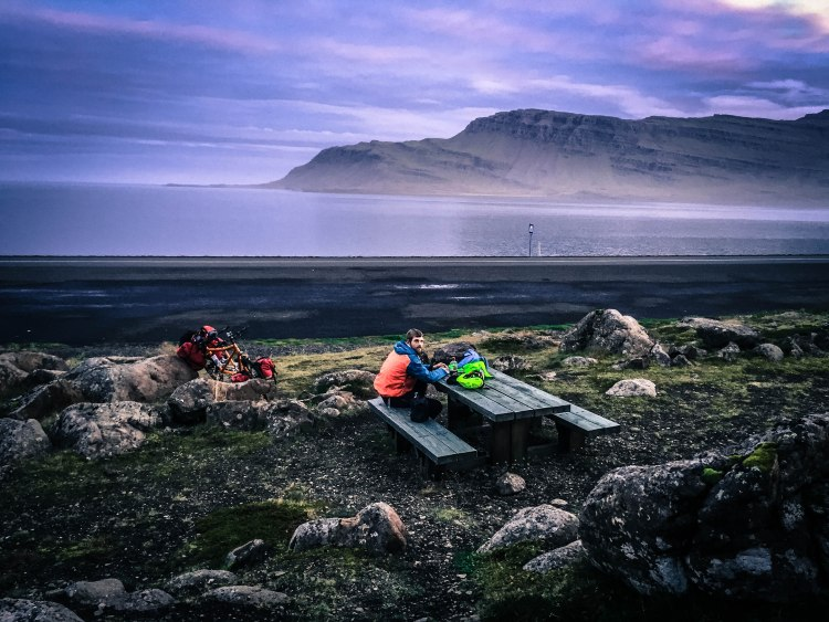 A man sitting on a bench in a fjord in Iceland