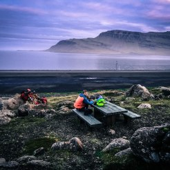 Man sitting on bench at a fjord in Iceland