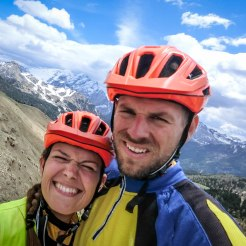 two bicycle rider with orange helmets in the Alpes during a Tandem Bicycle Tour